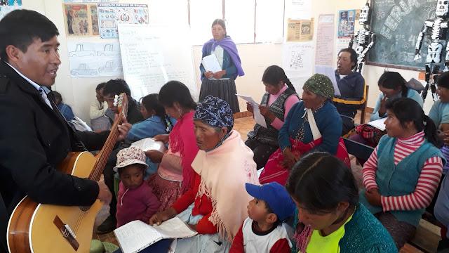Beim multifunktionalen Gottesdienst. Die Jugend zeigt, wie sie die Erweckung des Lazarus gezeichnet hat. Der Lehrer übt während dessen Lieder mit den Erwachsenen.