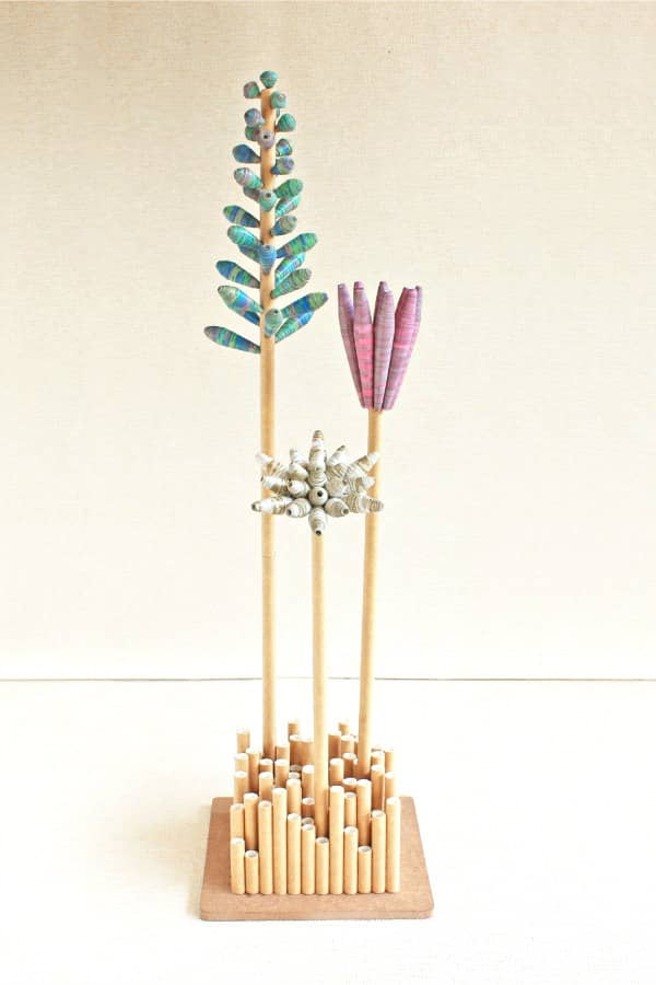 bouquet of minimal paper bead flowers displayed in vase composed of upright, hollow paper tubes in varied sizes