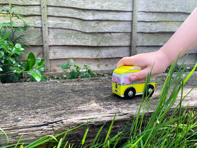 A wooden campervan Peppa pig toy being pushed along a railway beam