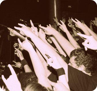 Illusztráció vershez, fekete-fehér, metálvillát rázó, dalszöveget ordító tömeg foglalja el a teret egy punk, rock vagy metal koncert küzdőterén.