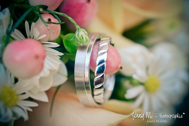 photos alliances des mariés posées sur bouquet de mariée