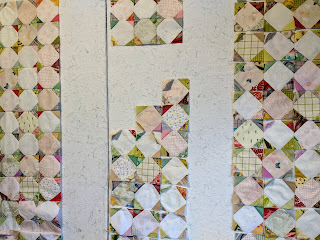 Quilt borders of three rows of pale snowball blocks with soft colors in the corners are in the process of being constructed