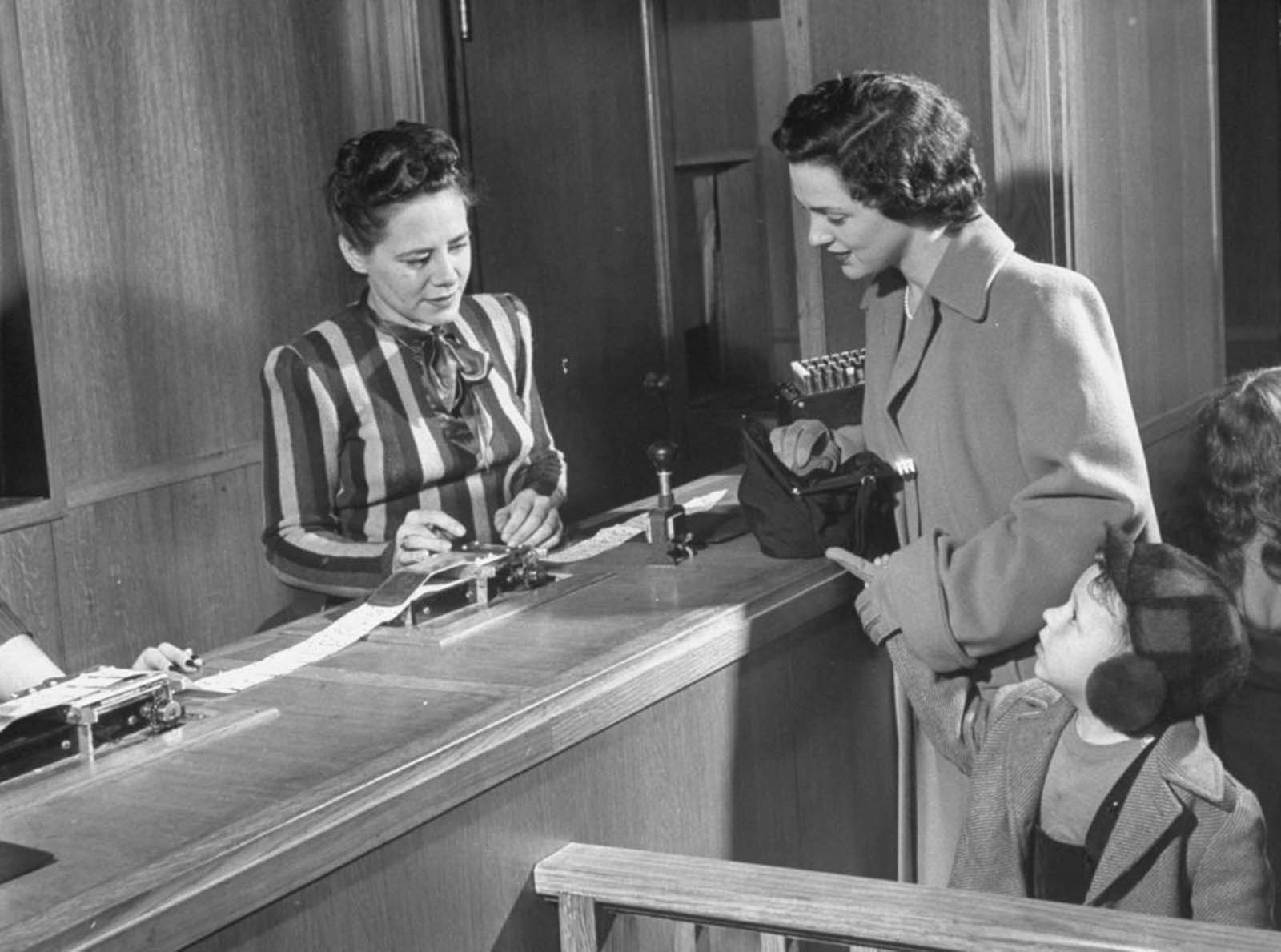 The shopper gives a punched-out card to the cashier, who totals the prices and triggers machinery behind the scenes.
