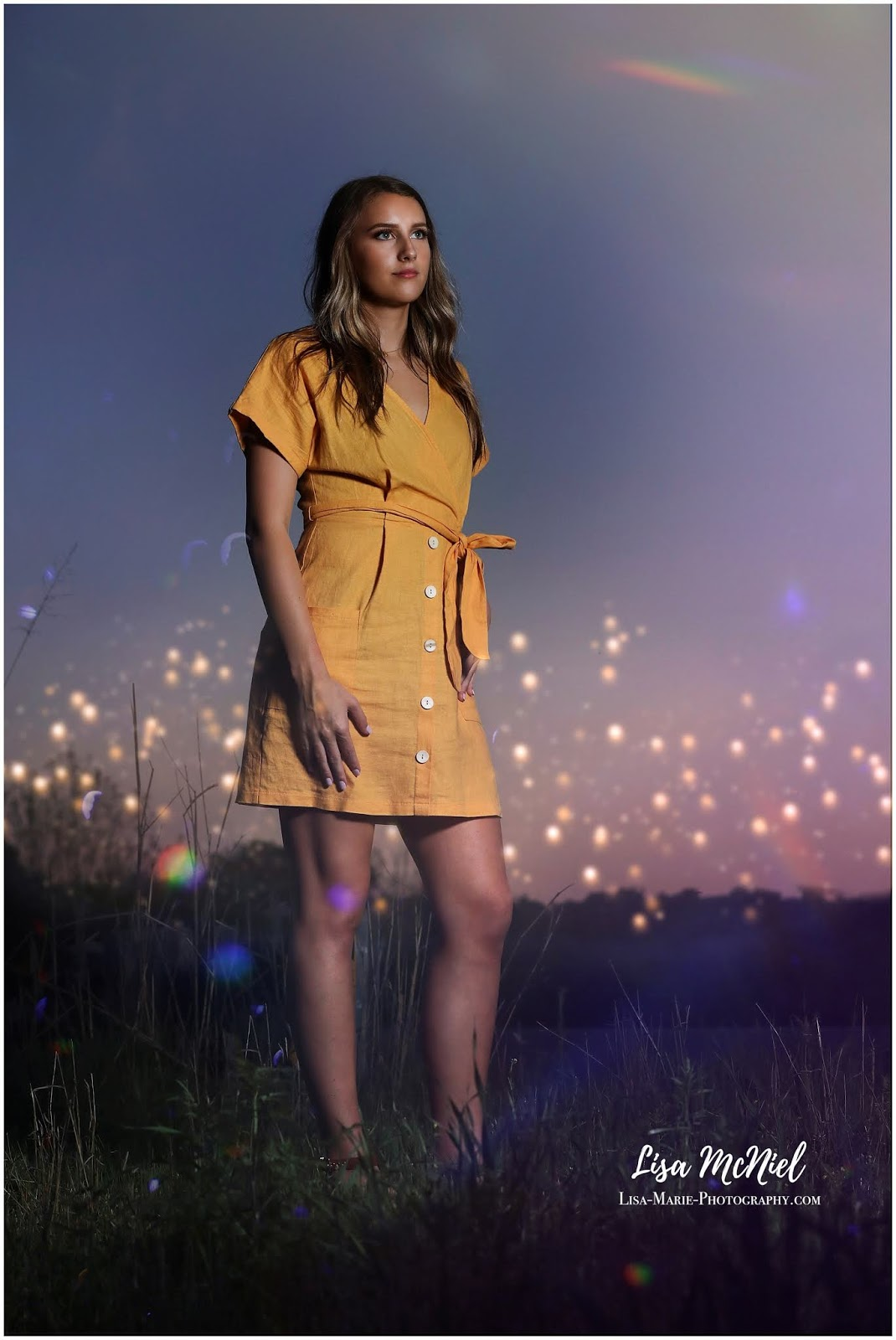 teen girl standing in grass at night with lights behind her