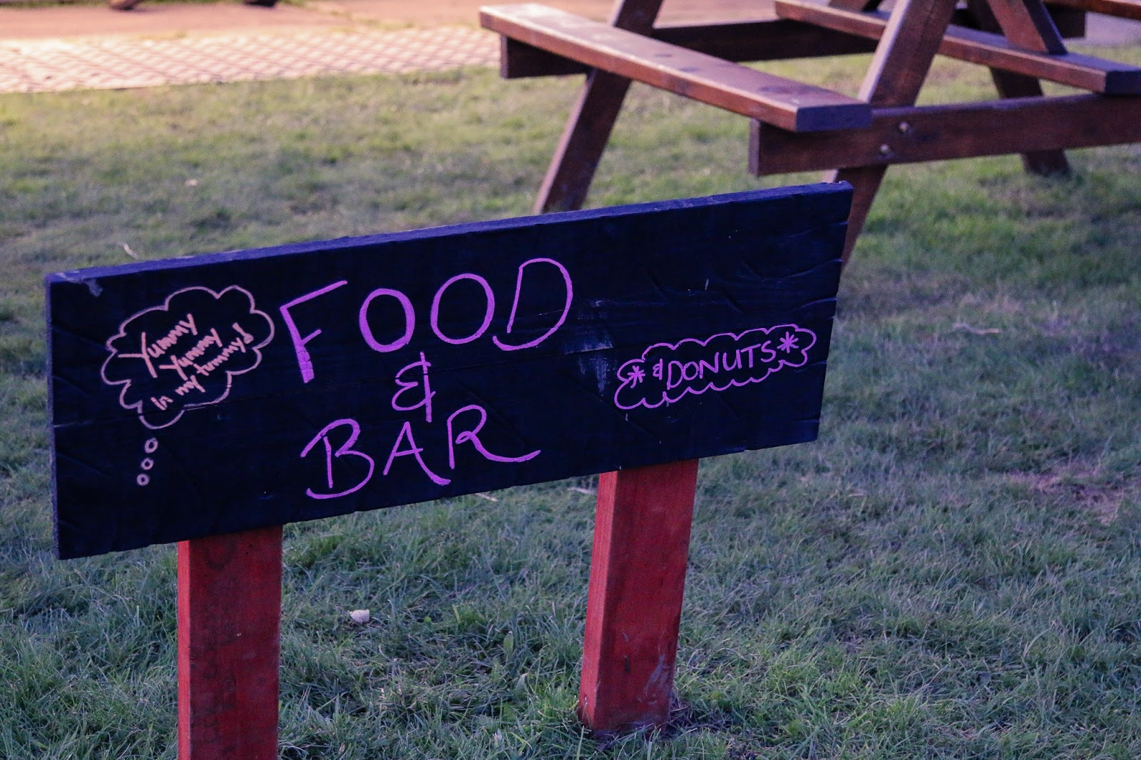 "Close up photo of the sign for the Food and bar area at M&D's pumpkin festival - A slate sign with ""Food and Bar"" written on it."