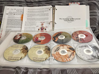 Open Bodhi Yoga teacher training manual and open media kit filled with CDs and DVDs.