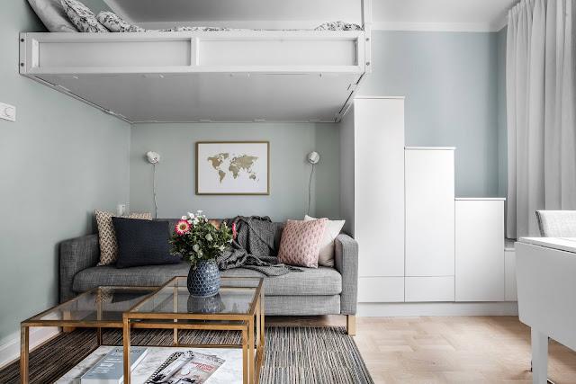 Pat deasupra canapelei și scări din spații de depozitare în amenajarea unei garsoniere de 22 m²
