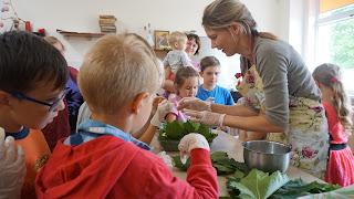 Nuotraukoje vaikai apsupę Labardžių bibliotekininkę mokosi kepti duoną. užsiėmimas