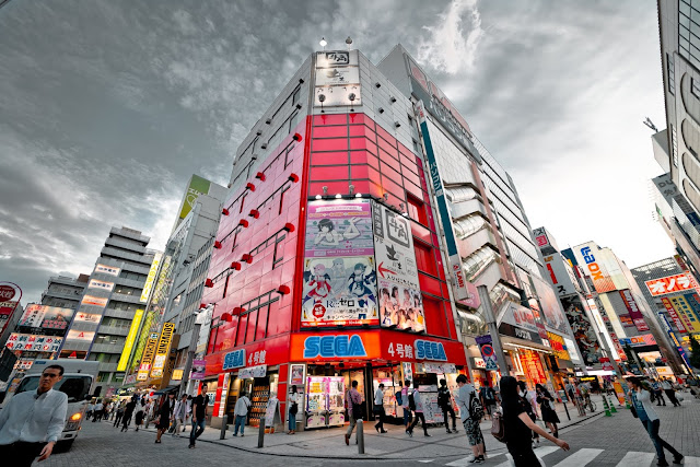 A place in Akihabara Electric Town, Tokyo, Japan with people crossing streets near SEGA red building and other establishments full of anime billboards