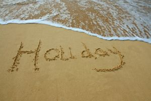 the word 'holiday' written in the sand