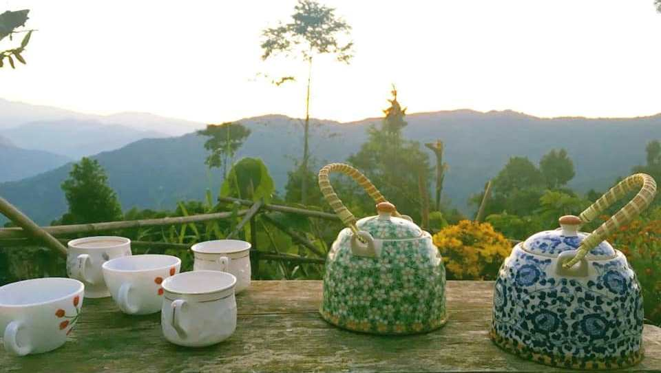 Two tea pot with five white cup and a spectacular view from Home stay in Darjeeling