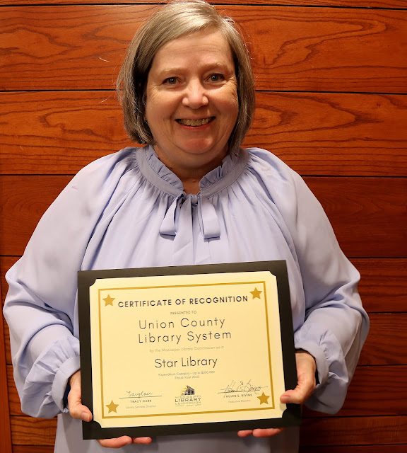 smiling woman holds star recognition certificate for union county library system