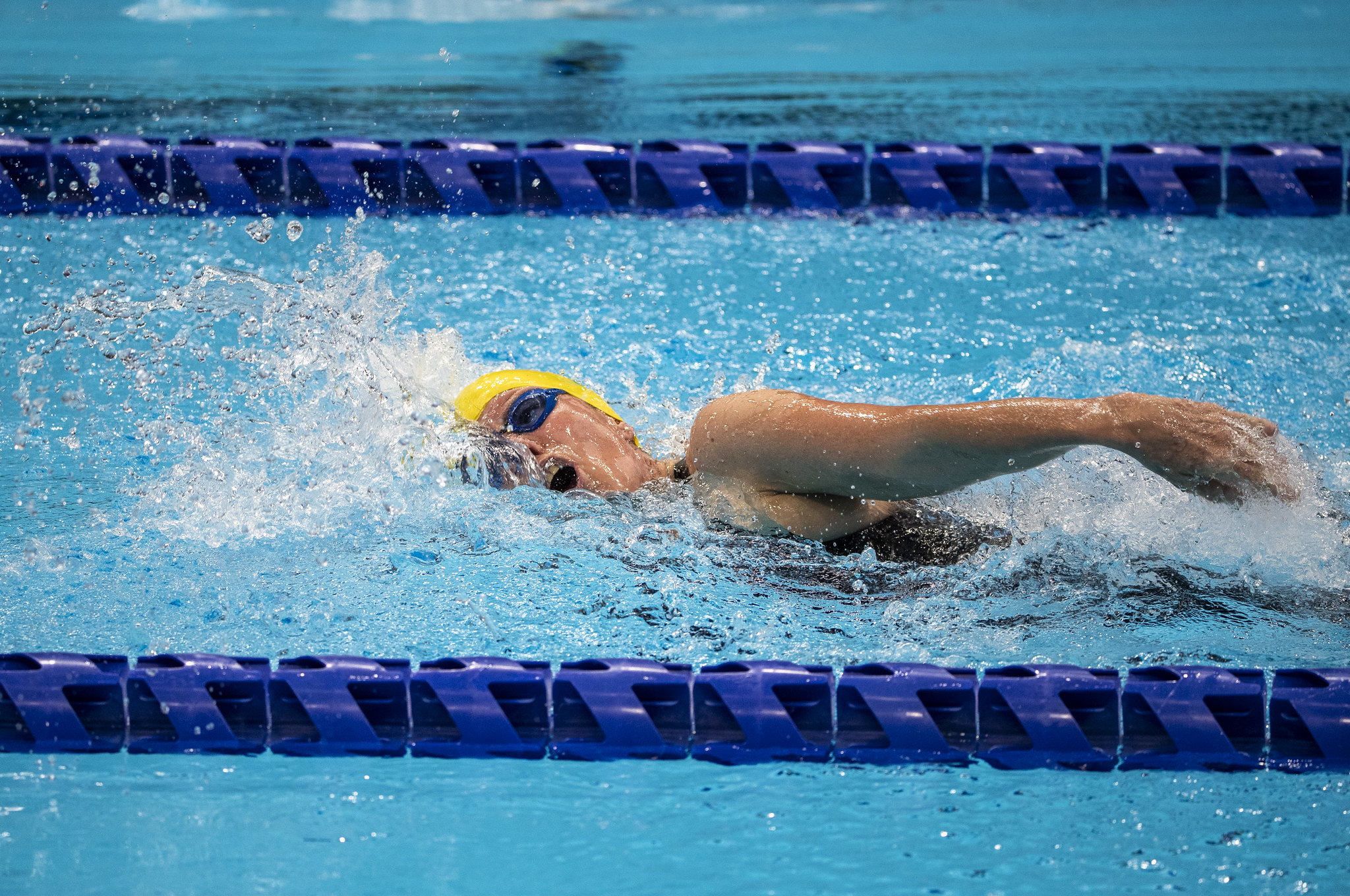 Susana Schnarndorf nada no meio da raia de óculos azul e touca amarela