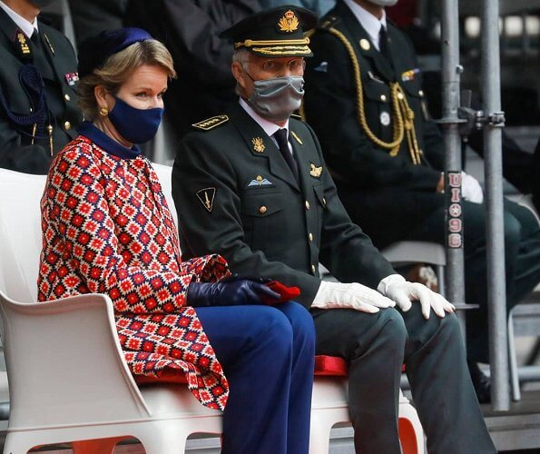 Crown Princess Elisabeth. Queen Mathilde wore a blue suit, high neck belted top and blue trousers, and red print collarless coat jacket