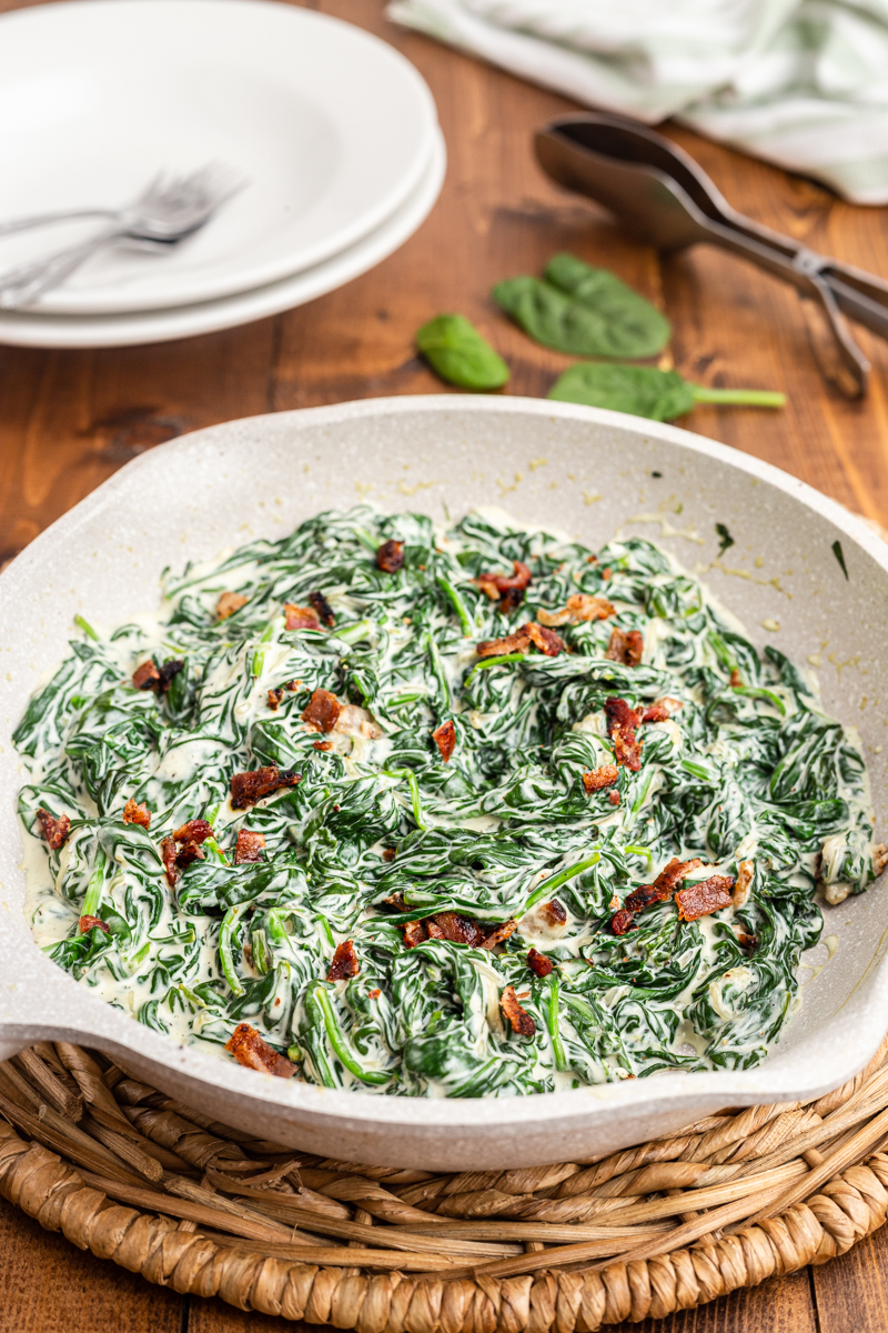 Photo of completed Easy Creamed Spinach recipe in a white skillet on a wooden table.