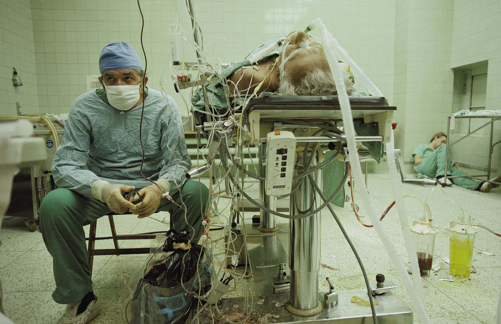 Dr. Zbigniew Religa monitors his patient's vitals after a 23 hour long heart transplant surgery. His assistant is asleep in the corner.