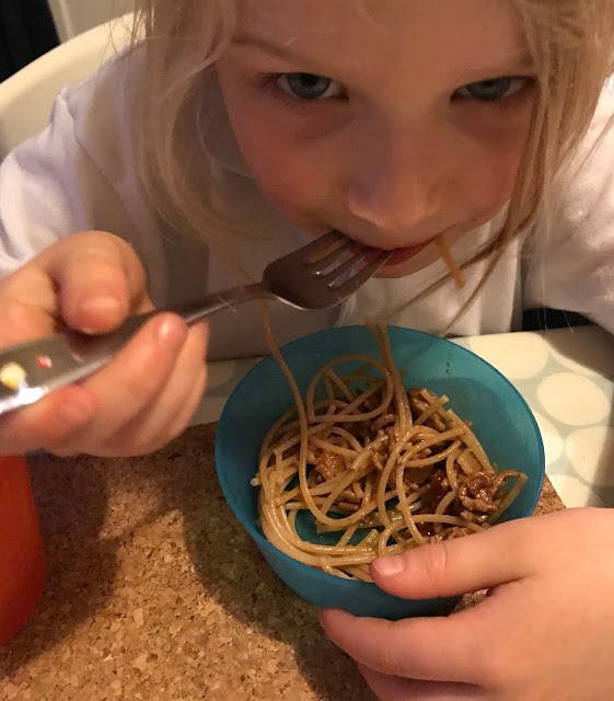 A young girl eating a bowl of spaghetti bolognese