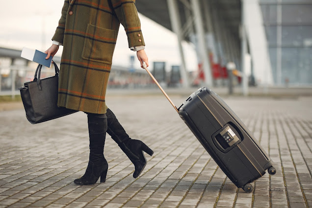 https://www.pexels.com/photo/stylish-woman-with-suitcase-and-bag-walking-on-street-near-modern-airport-terminal-3885493/