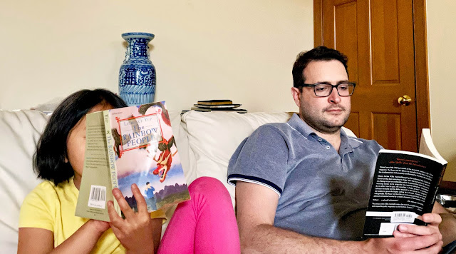 My niece and husband are reading side by side on a couch. The girl's face is covered by her open book (The Rainbow People), while the man's face is concentrated on the book in his lap (The Power and the Glory).