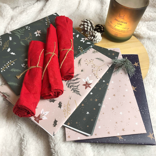 Four red napkins rolled up on top of multicolour Christmas wrapping paper next to a lit candle