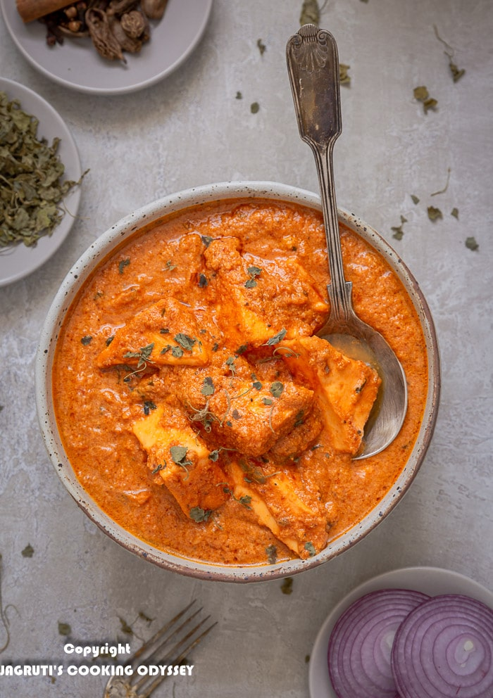 Bowl of paneer tikka masala served with a serving spoon next to a small bowl of chopped red onion salad