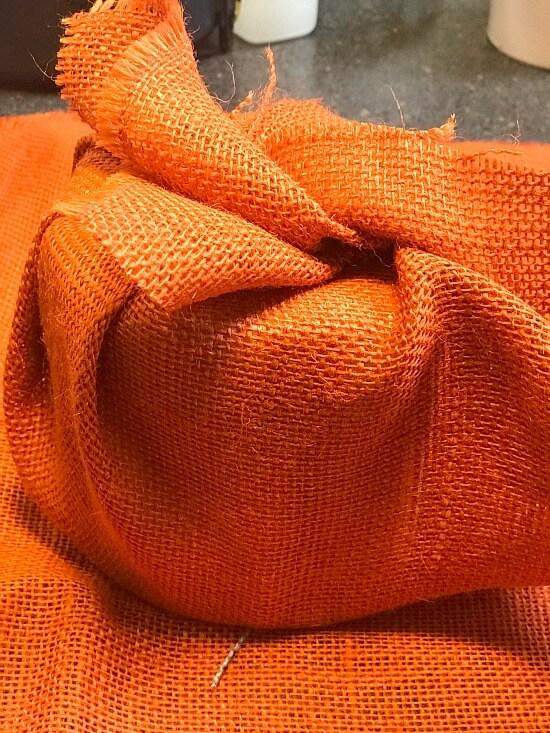 Orange burlap wrapped around toilet paper roll.