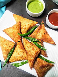 Onion samosa with fried green chili. Green chutney and sweet chutney in background