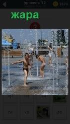 Дети в городе в жару прыгают под фонтаном