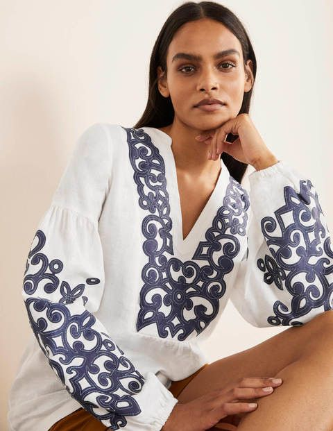 White long sleeved blouse with blue embroidery