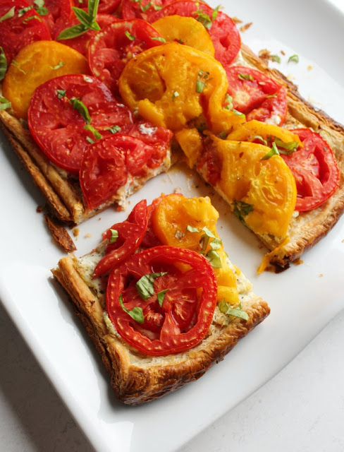 corner slice of flaky ricotta and tomato tart with yellow and red tomatoes and fresh basil on top