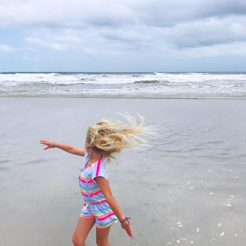 Little girl dancing on the beach
