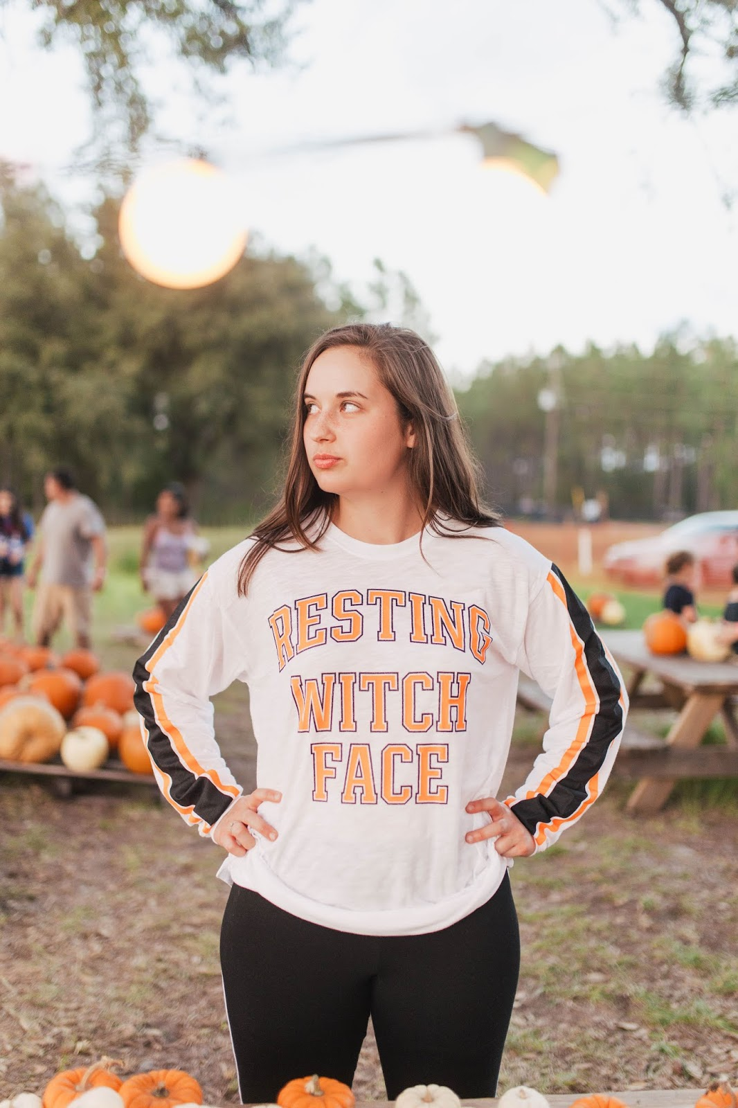 Brunette girl wearing Victoria's Secret Pink Resting Witch Face Campus Long Sleeve Tee at pumpkin patch in jacksonville florida