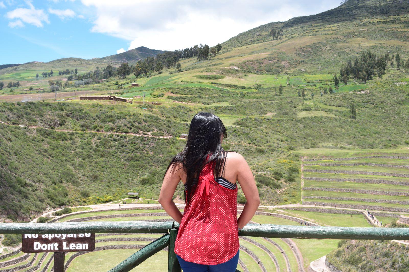 mulher de costas em sitio arqueologico da agricultura inca de escadarias