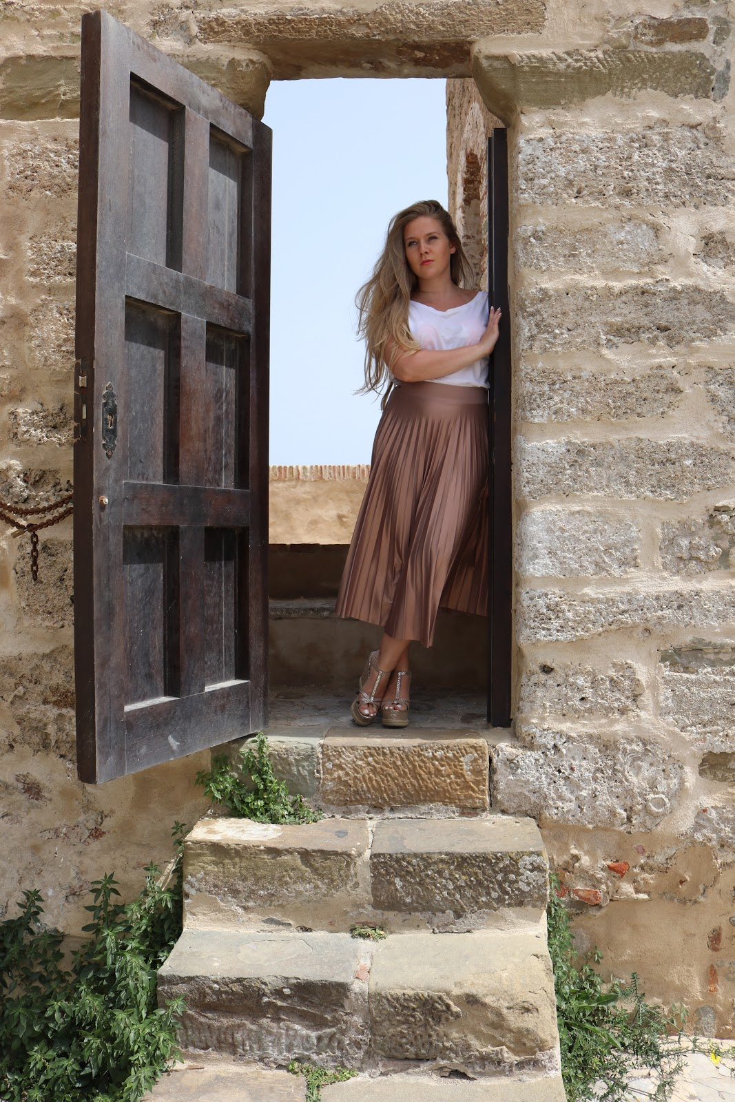 Blonde girl wearing metallic skirt standing in a doorway in Tarifa, Spain