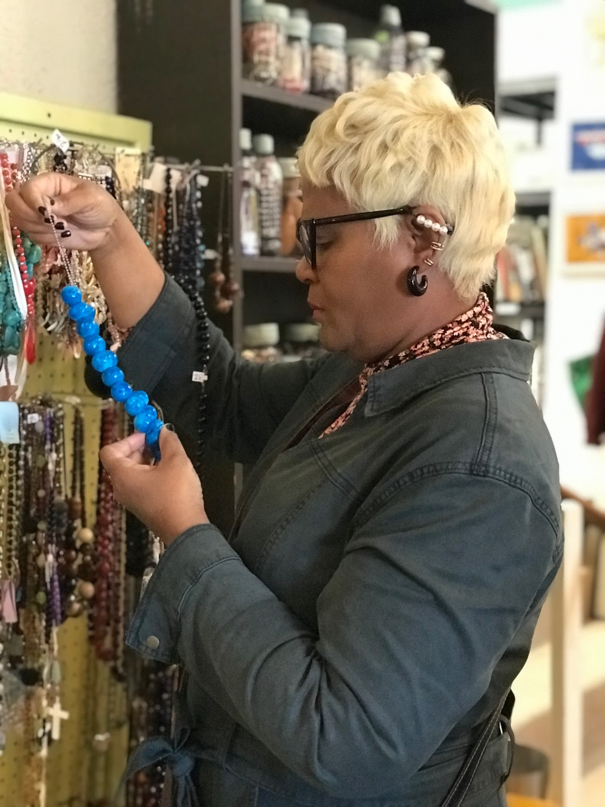 Tangie Bell trying on marble secondhand jewelry. Thrift snooping