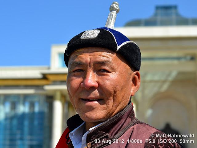 people, portrait, headshot, street portrait, Mongolia, Ulaanbaatar, Chinggis Khaan Square, Mongolian man, traditional Mongolian costume, traditional Mongolian hat, Mongolian deel