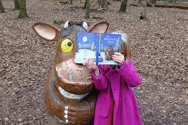 A wooden carving of the Gruffalo's child next to a girl in a pink coat holding the gruffalo's child book up
