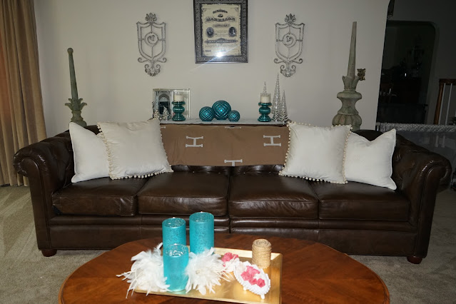H Blanket, velvet pillows with pom poms, French provincial coffee table, rose soaps, milk glass bowl, glass globes, and feathers