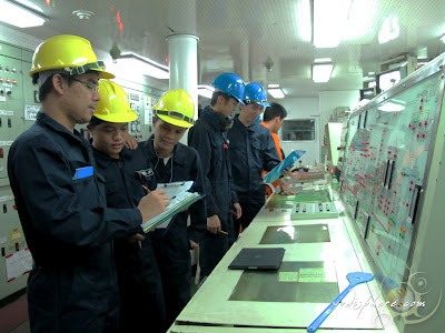 Cadets and officers at the ship engine control room