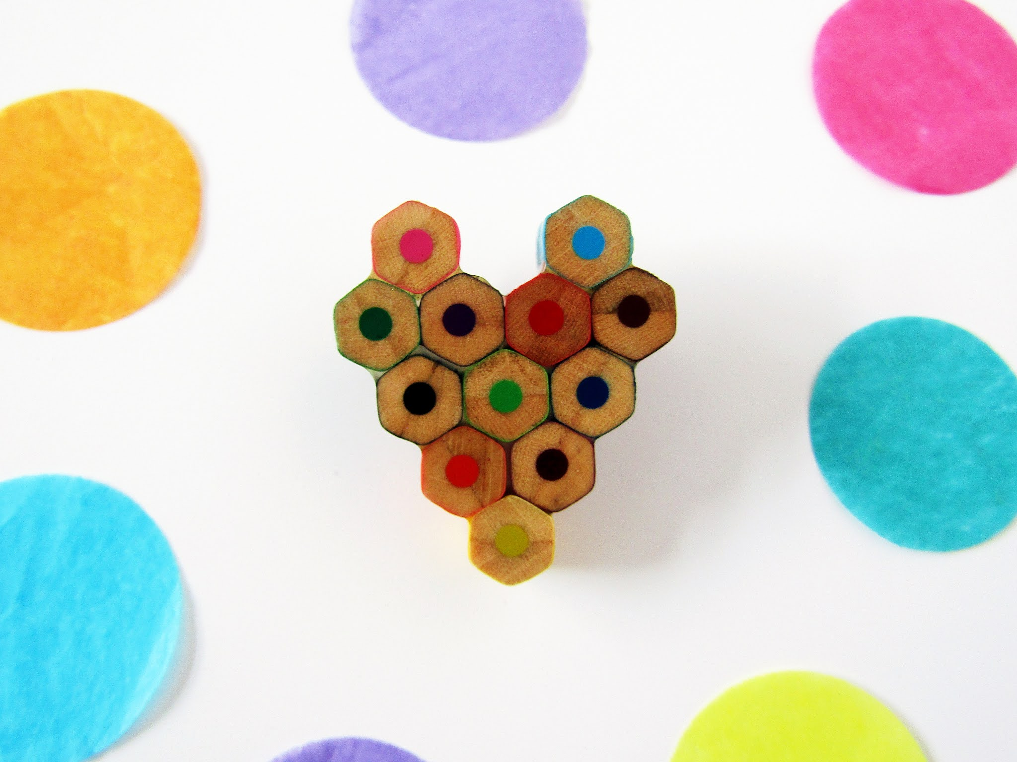 A photo of a wooden heart-shaped brooch made from the ends of colourful pencils.