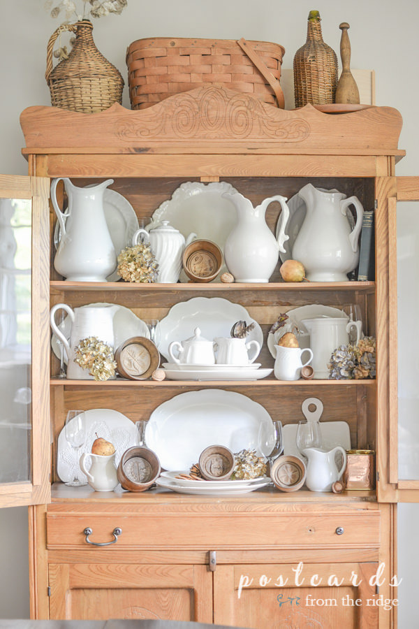 wooden butter molds and white ironstone in antique oak hutch