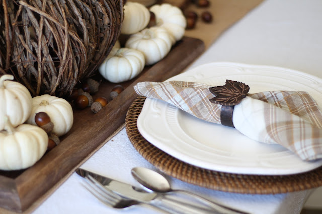 Natural fall tablescape with cream plates rattan chargers and plaid napkins