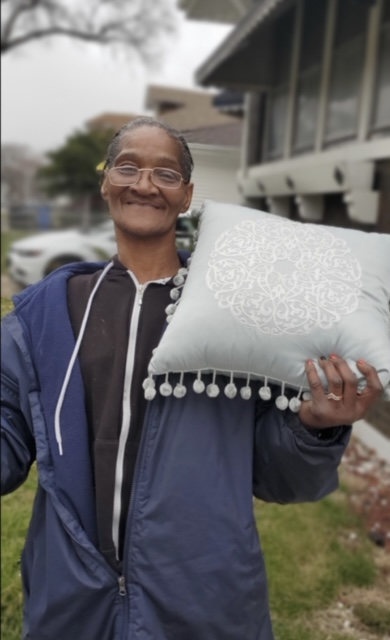 The pillow this neighbor is holding is one of the many items gifted to a neighbor moving into a new home! Image Credit Bisma Shoukat.