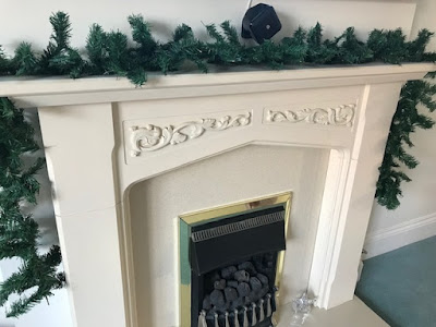 Plain green garland over a fireplace