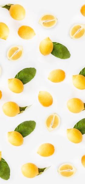 خلفية ثمار الليمون الصفراء الطازجة المتناثرة على سطح أبيض