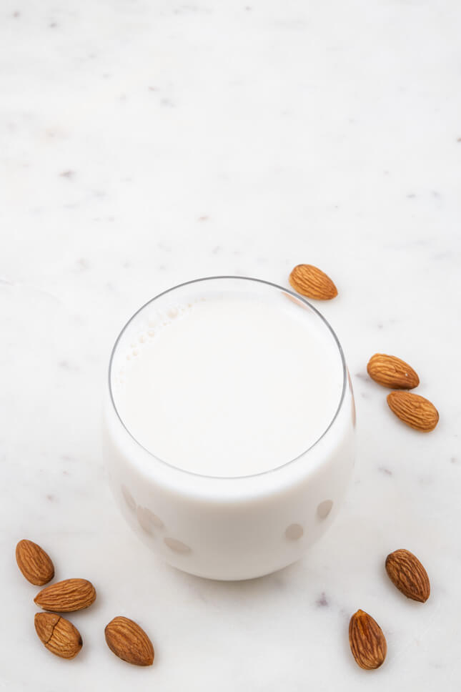 Photo of a glass of almond milk with decorating almonds around
