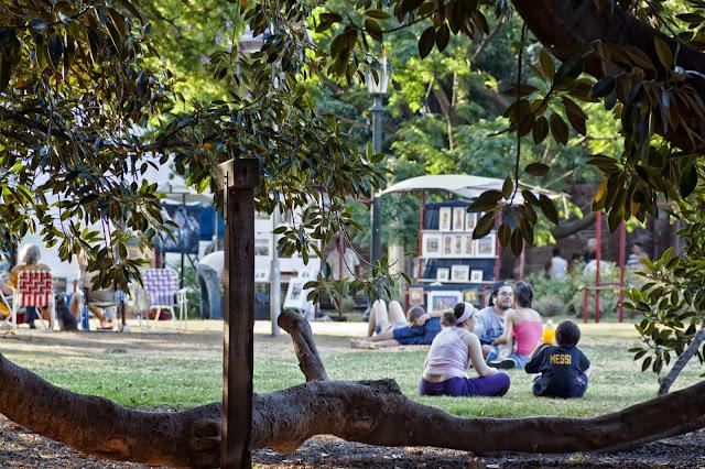 Gente sentada al sol en la plaza.
