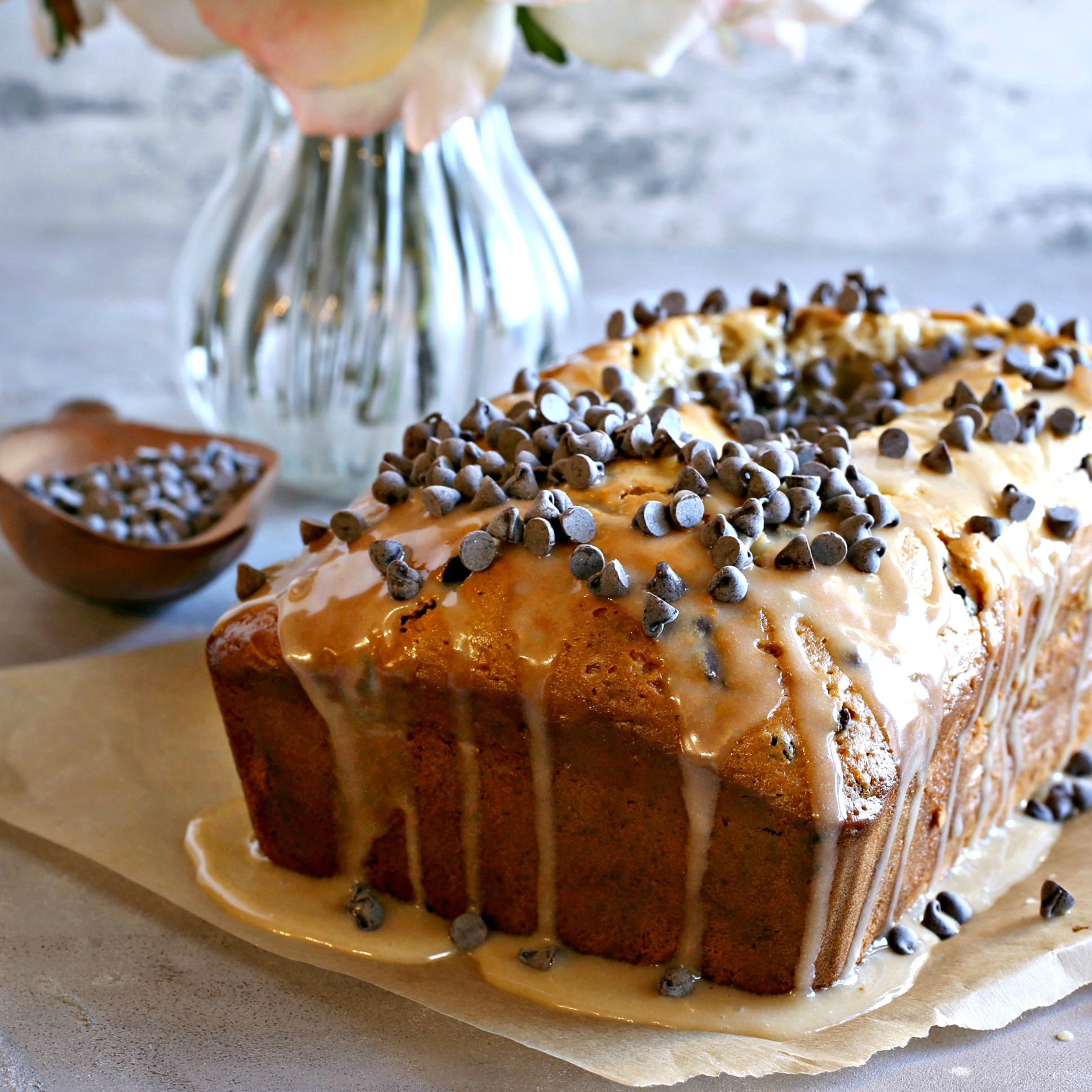 Recipe for a chocolate chip loaf cake flavored with sesame tahini and topped with a sweet tahini glaze.