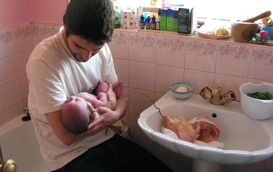 Babai duke mbajtur fëmijën e sapolindur