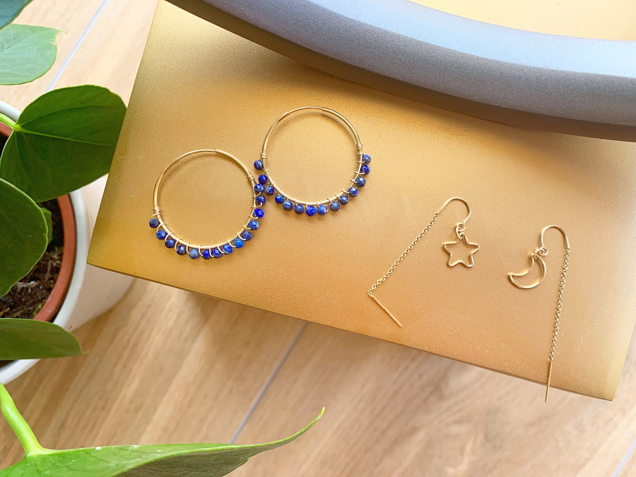 Binichohan Threader Earrings and Lapis Hoop Earrings on a gold background